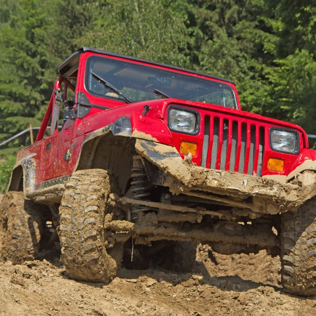 Red off-road vehicle in muddy terrain. All potential trademarks are removed.
